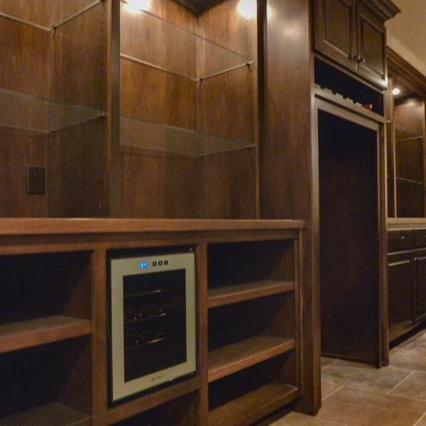 Home bar with custom cabinets, glass shelves and wine refrigerator