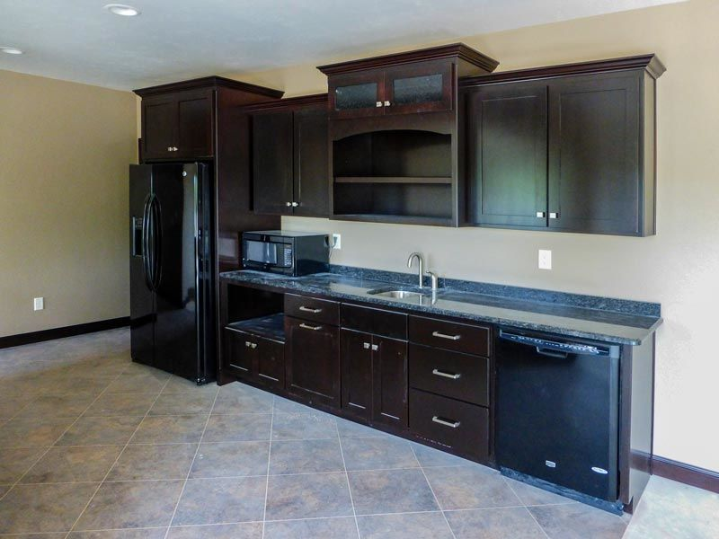 Home bar with refrigerator, sink, cabinet and counter space