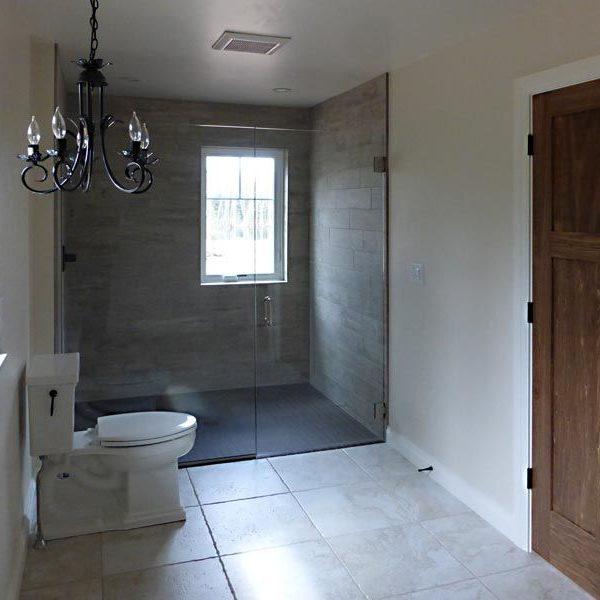 Bathroom with floor to ceiling shower with glass door
