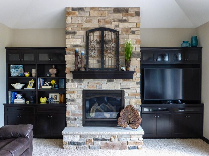 Floor to ceiling stone fireplace with built in cabinets on each side