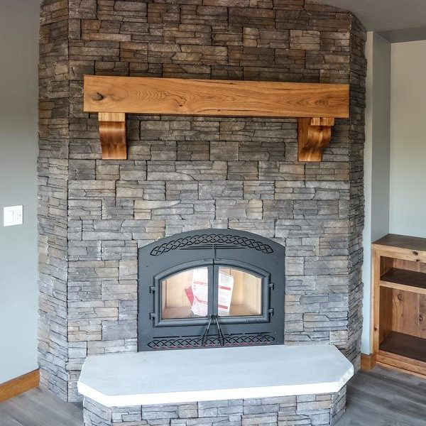 Floor to ceiling stone fireplace with wooden mantel