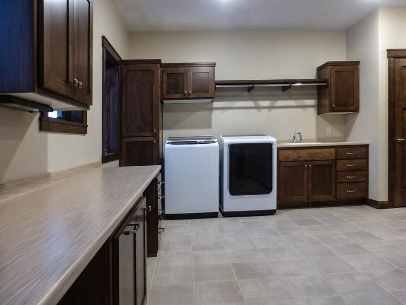 Laundry room with sink, washer, dryer, cabinets, utility closet, and large counter space for folding clothes