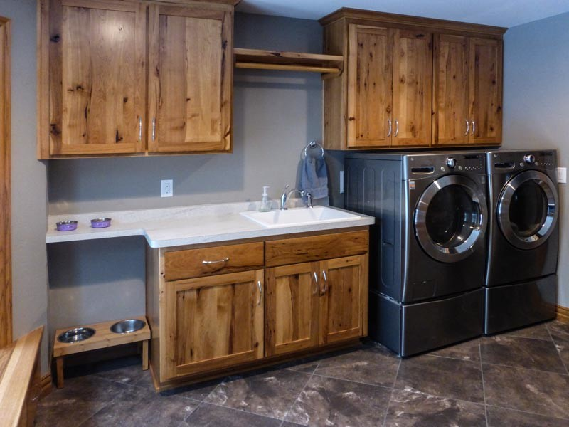 Laundry room with sink, washer, dryer, cabinets, and dog food station