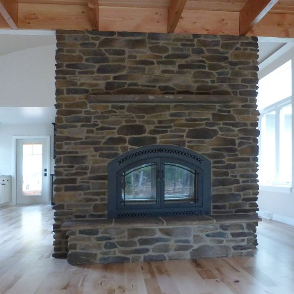 Floor to ceiling stone fireplace separates living room and kitchen
