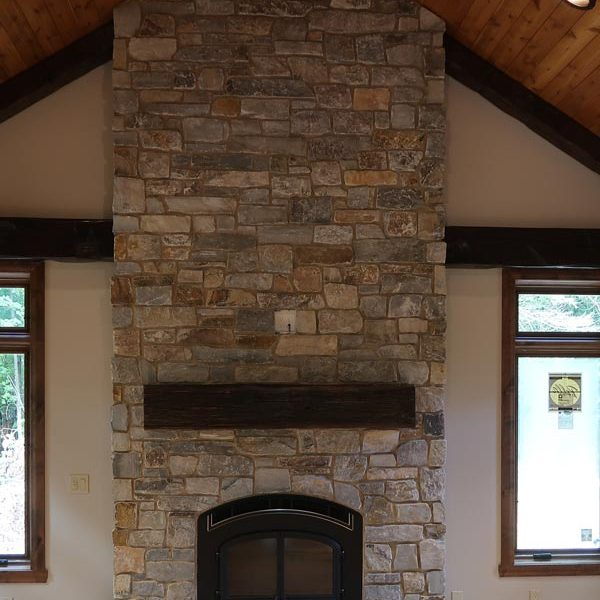 Floor to ceiling stone fireplace with mantel