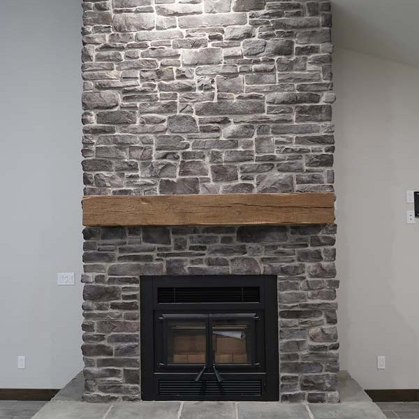 Floor to Ceiling Stone Fireplace with Beam Shelf